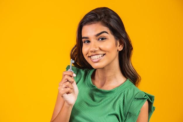 Молодая женщина, держащая ключ от нового дома.