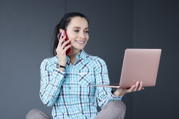 젊은여자가 그녀의 손에 노트북을 들고와 전화 통화. 프리랜서 작업 개념