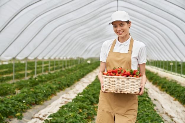 大きなおいしい赤いイチゴを持っている若い女性