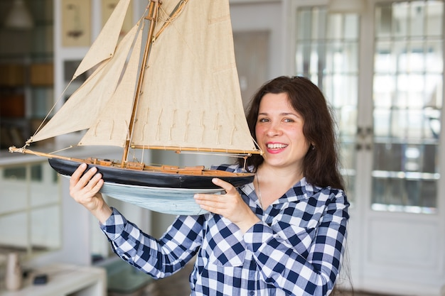 Young woman holding layout of a sailboat