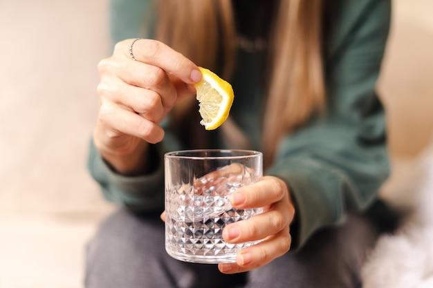 Молодая женщина, держащая ломтик лимона и стакан воды, крупным планом