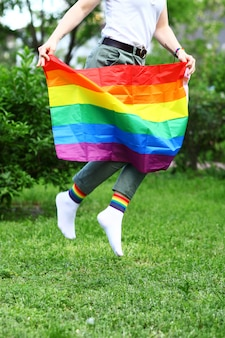 Young woman holding lgbtq flag in nature