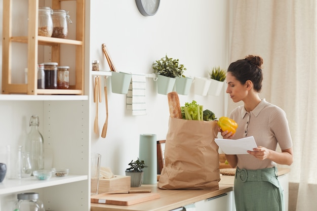 Young woman holding list and looking at vegetables in paper bag while standing in the kitchen