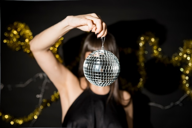 Young woman holding little disco ball near tinsel