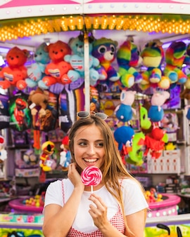 Young woman holding lollipop in her hand standing in front of toy shop