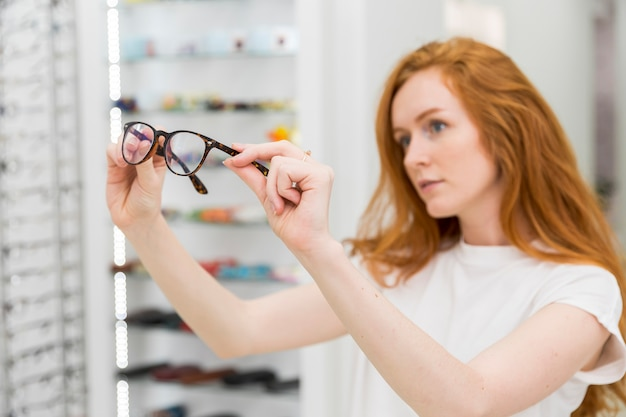 Young woman holding and looking at spectacle in optica