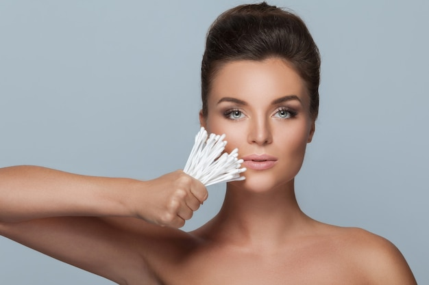 Young woman holding lot of cotton swabs in her hand