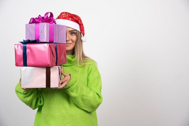 Giovane donna che tiene molti regali di natale festivi.
