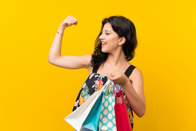 Young woman holding a lot of shopping bags