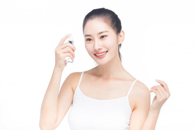 顔にローションボトルとスプレーを保持している若い女性