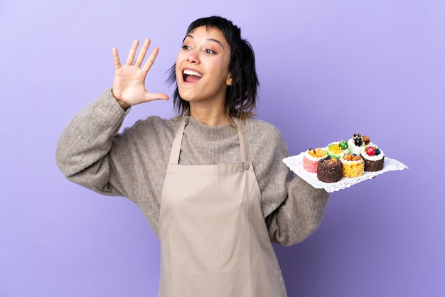 Young  woman holding lots of different mini cakes over isolated purple space shouting with mouth wide open