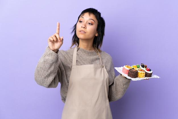 Young woman holding lots of different mini cakes over isolated purple touching on transparent screen