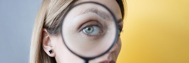 Young woman holding magnifying glass in front of her eye closeup