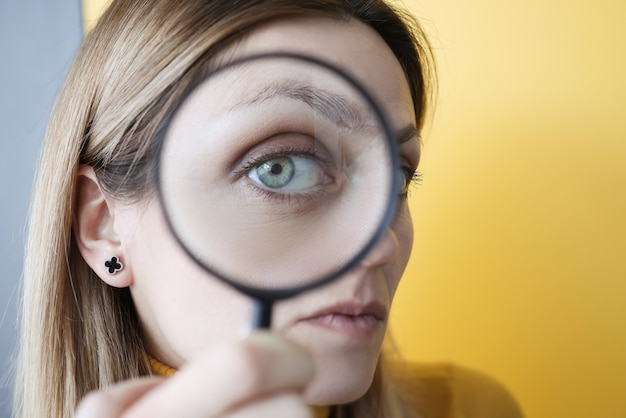 그녀의 눈 근접 촬영 앞에서 돋보기를 들고 젊은 여자
