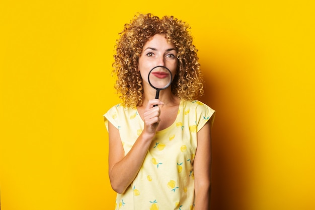 Young woman holding a magnifying glass near her mouth on a yellow surface