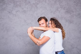 Young woman holding man from behind