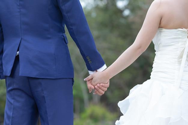 Молодая женщина держит мужчину за руку, ведя его по цветнику