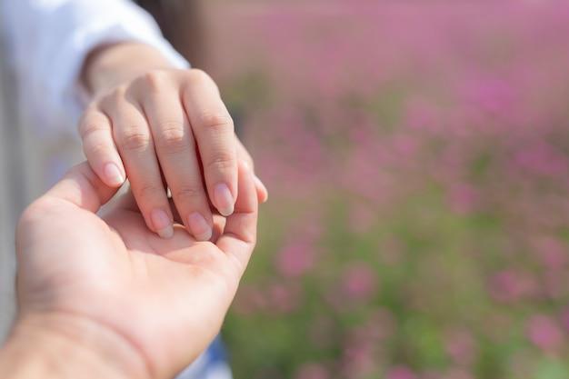 꽃 정원에서 그를 이끌면서 남자 손을 잡고 젊은 여자