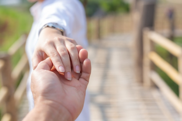 花の庭で彼を導きながら男の手を握る若い女性