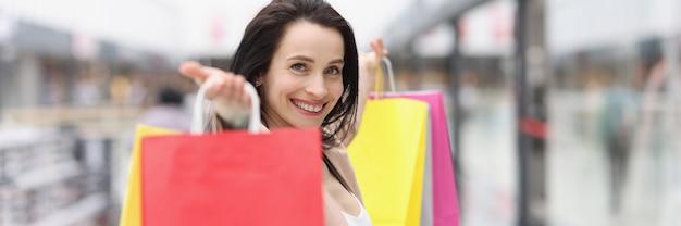 色とりどりの買い物袋をたくさん持っている若い女性