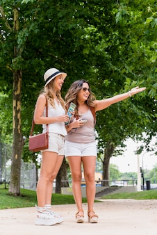 Young woman holding map in hand looking at her smiling friend showing something in the park