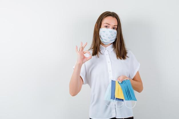 Giovane donna che tiene le maschere mediche e che mostra il segno giusto