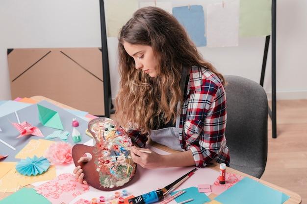 Молодая женщина держит грязную деревянную палитру акварели и кисть