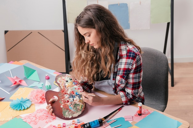 Young woman holding messy wooden watercolor palette and paintbrush