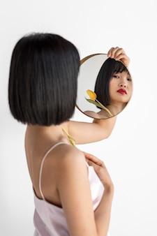 Молодая женщина, держащая зеркало