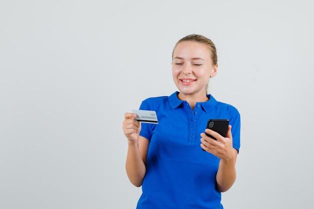 파란색 티셔츠에 휴대 전화와 플라스틱 카드를 들고 행복을 찾는 젊은 여자