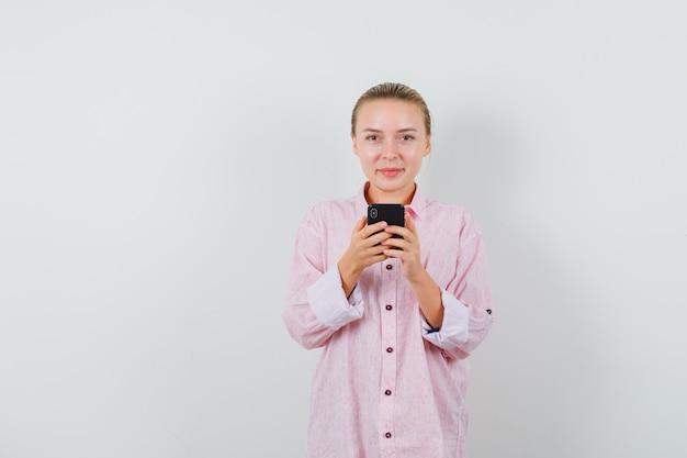 携帯電話を持ってピンクのシャツに笑みを浮かべて若い女性