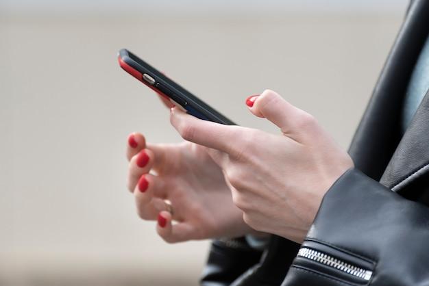 携帯電話を保持している若い女性。手でスマートフォンを持つ女性実業家