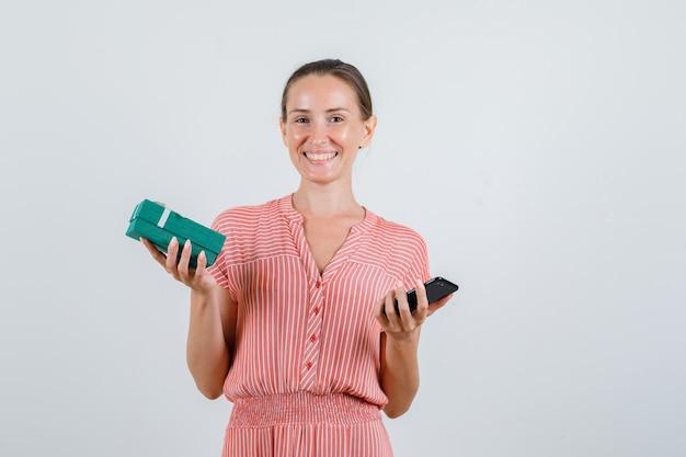 Giovane donna che tiene il telefono cellulare e il contenitore di regalo in vestito a strisce e che sembra allegro. vista frontale.