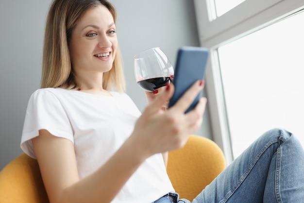그녀의 손에 휴대 전화를 들고 집에서 유리에서 레드 와인을 마시는 젊은 여자