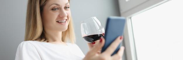 휴대전화를 손에 들고 집에서 유리잔으로 적포도주를 마시는 젊은 여성