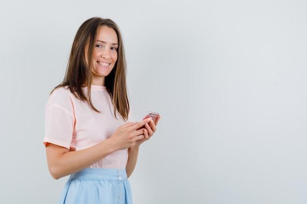 Tシャツ、スカート、陽気に見える携帯電話を保持している若い女性。正面図。