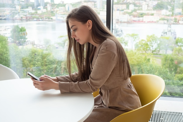 Young woman holding a mobile phone while sitting in a cafe by the window