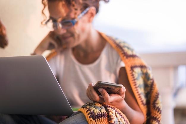 노트북에서 작업하는 동안 휴대 전화를 들고 젊은 여자. 집 테라스에 앉아 노트북 작업을 하는 여자. 휴대전화를 들고 노트북을 사용하여 좋은 소식을 듣고 기뻐하는 여성