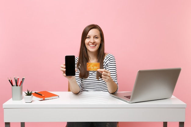 Young woman holding mobile phone with blank empty screen and credit card sit work at white desk with contemporary pc laptop