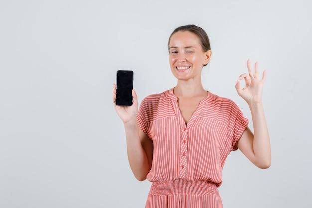 Giovane donna che tiene il telefono cellulare con il segno giusto in vestito a strisce e che sembra allegro. vista frontale.