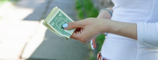 공원에서 그녀의 손에 돈을 들고 젊은 여자