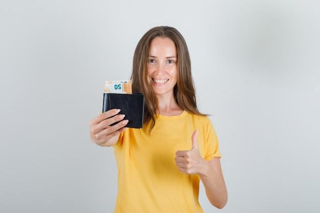 黄色のtシャツに親指を立てて財布にお金を保持し、陽気に見える若い女性