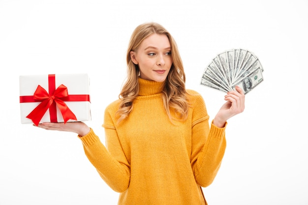 Young woman holding money and surprise gift box.