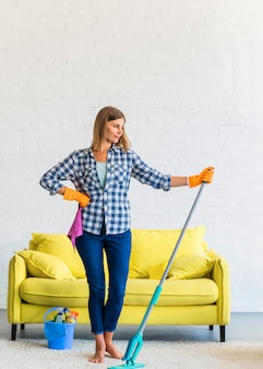 Young woman holding mop in hand standing in front of yellow sofa