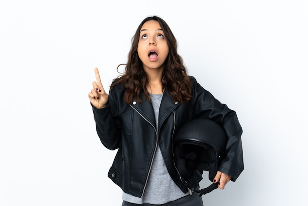 Young woman holding a motorcycle helmet isolated pointing up and surprised