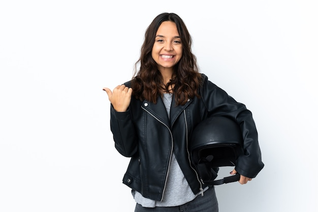 Young woman holding a motorcycle helmet over isolated white background pointing to the side to present a product