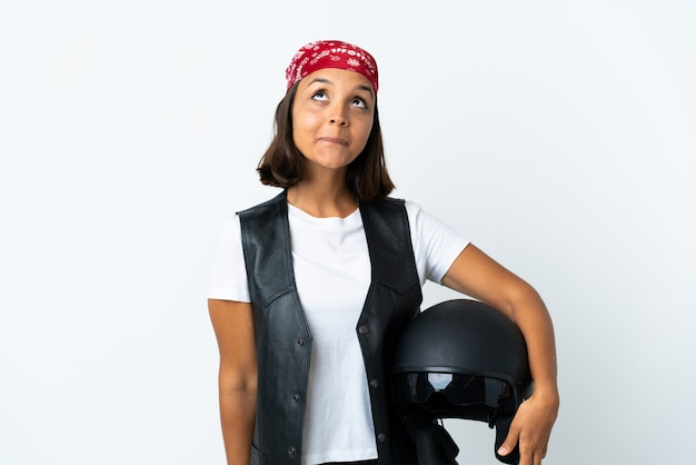 Young woman holding a motorcycle helmet isolated on white and looking up