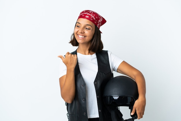 Young woman holding a motorcycle helmet isolated on white pointing to the side to present a product