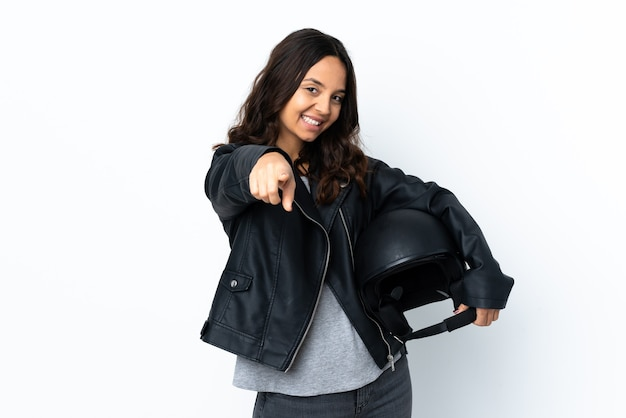 Young woman holding a motorcycle helmet over isolated white points finger at you with a confident expression