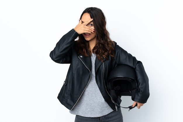 Young woman holding a motorcycle helmet over isolated white wall covering eyes by hands and smiling